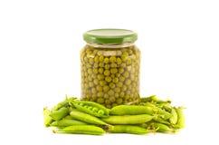 Las verduras de los guisantes verdes conservaron preservado en los potes de los tarros del vidrio aislados en blanco Fotografía de archivo