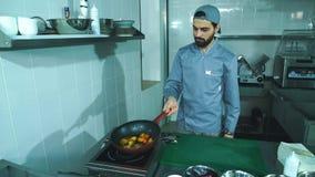 Las verduras frescas de la fritada del cocinero en una cacerola almacen de metraje de vídeo