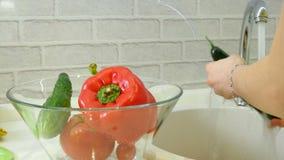 Las verduras frescas de los lavados de la mujer debajo del golpecito en el fregadero en la cocina los ponen en una taza de crista almacen de metraje de vídeo
