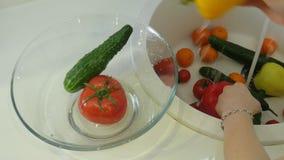 Las verduras frescas de los lavados de la mujer debajo del golpecito en el fregadero en la cocina los ponen en una taza de crista almacen de video
