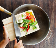 Las verduras frescas en la tabla de cortar están cayendo en el wok. Co Fotos de archivo
