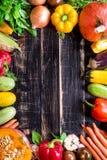 Las verduras frescas en una oscuridad rústica texturizaron la tabla Backgro del otoño Foto de archivo