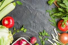 Las verduras frescas y los verdes en manojos arreglaron en un marco en un fondo de piedra negro Fotos de archivo