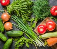 Las verduras frescas y los verdes en manojos arreglaron en un marco en un fondo de piedra negro Fotografía de archivo libre de regalías