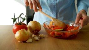 Las verduras tajadas frescas de la mezcla de la mujer joven en un bol de vidrio almacen de metraje de vídeo