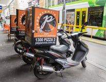 Las vespas para la entrega de la pizza parquearon fuera de una tienda de pizza en Melbourne Imágenes de archivo libres de regalías