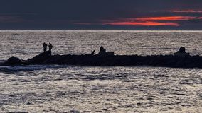 Las vidas de la gente en el acantilado en la puesta del sol en el mar foto de archivo