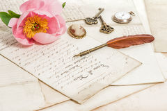 Las viejas letras, la flor rosada de la peonía y la antigüedad empluman la pluma vendimia Fotografía de archivo