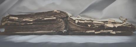 Las viejas mentiras desaliñadas antiguas del ` de la biblia del ` del libro se abren en la tabla con la pañería blanca El concept Imagen de archivo
