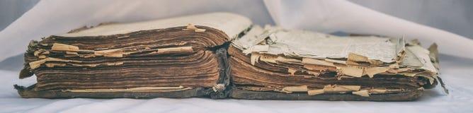 Las viejas mentiras desaliñadas antiguas del ` de la biblia del ` del libro se abren en la tabla con la pañería blanca El concept Imagen de archivo libre de regalías