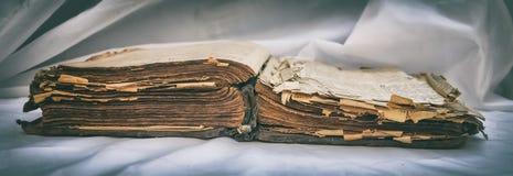 Las viejas mentiras desaliñadas antiguas del ` de la biblia del ` del libro se abren en la tabla con la pañería blanca El concept Fotos de archivo