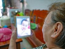 Las viejas mujeres asiáticas muy felices miran la tableta en su casa foto de archivo