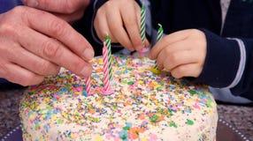 Las viejas y jovenes manos pusieron velas en una torta Fotos de archivo libres de regalías