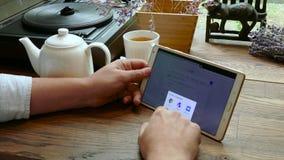 Las visitas Google del hombre buscan sitio web en la PC de la tableta en un café metrajes