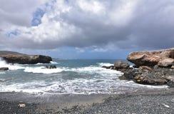 Las vistas escénicas del ` s de Aruba ennegrecen la playa de piedra de la arena Imagenes de archivo