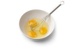 Las yemas de huevo en un cuenco con baten Fotos de archivo