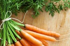 Las zanahorias agrupan en la madera foto de archivo