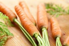 Las zanahorias agrupan en la madera fotografía de archivo