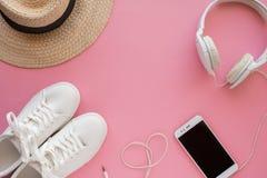 Las zapatillas de deporte blancas, sombrero de paja, auriculares, smartphone están mintiendo en un fondo rosado brillante imágenes de archivo libres de regalías