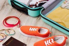 Las zapatillas de deporte coloreadas cerca abrieron la maleta Fotografía de archivo libre de regalías