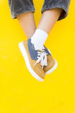 Las zapatillas de deporte de las piernas en el fondo amarillo, moda de la forma de vida Imagen de archivo