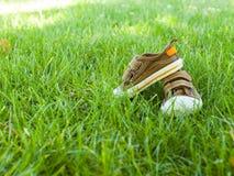 Las zapatillas de deporte del bebé están en la hierba Imagen de archivo libre de regalías
