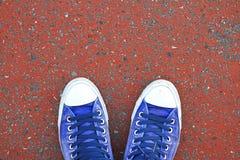 Las zapatillas de deporte en la tierra, exploran el concepto del mundo Foto de archivo libre de regalías