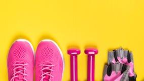 Las zapatillas de deporte, los guantes y las pesas de gimnasia rosados mienten en fila en un fondo amarillo, un lugar para una in imagen de archivo