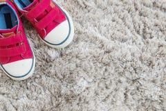 Las zapatillas de deporte rojas de la tela del primer del niño en la alfombra gris texturizaron el fondo en la visión superior co Imagen de archivo libre de regalías