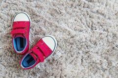 Las zapatillas de deporte rojas de la tela del primer del niño en la alfombra gris texturizaron el fondo en la visión superior co Foto de archivo libre de regalías