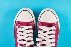 Las zapatillas de deporte rojas se acuestan en fondo azul Imagenes de archivo
