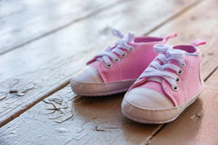 Las zapatillas de deporte rosadas lindas del bebé se cierran encima de exterior fotografía de archivo libre de regalías