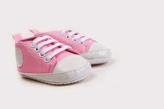 Las zapatillas de deporte rosadas lindas del bebé se cierran para arriba en gris fotografía de archivo