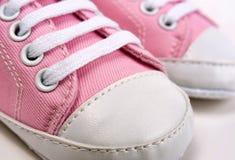 Las zapatillas de deporte rosadas lindas del bebé se cierran para arriba en gris fotografía de archivo libre de regalías