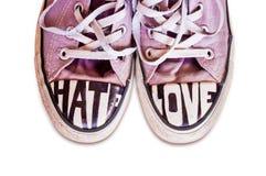 Las zapatillas de deporte rosadas usadas modificadas para requisitos particulares con palabras odian y aman Imagen de archivo