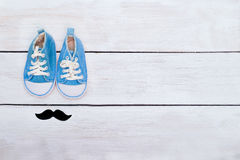 Las zapatillas de deporte y los bigotes azules del ` s del niño mienten en un backgr de madera blanco Fotos de archivo