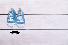 Las zapatillas de deporte y los bigotes azules del ` s del niño mienten en un backgr de madera blanco Imagenes de archivo