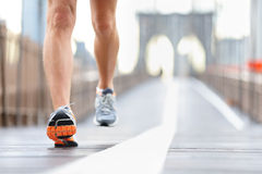 Las zapatillas deportivas, los pies y las piernas se cierran para arriba del corredor Foto de archivo