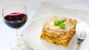 Lasañas con la salsa boloñesa en la placa blanca con el vino imagen de archivo