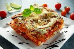Lasañas curruscantes hechas en casa en cacerola del hierro con la salsa boloñesa, el queso parmesano y la albahaca de la carne de Imágenes de archivo libres de regalías