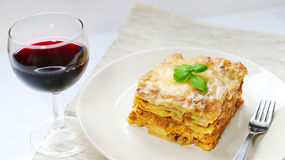 Lasagna με την από τη Μπολώνια σάλτσα στο άσπρο πιάτο με το κρασί Στοκ Εικόνα