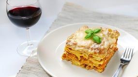 Lasagna με την από τη Μπολώνια σάλτσα στο άσπρο πιάτο με το κρασί Στοκ φωτογραφία με δικαίωμα ελεύθερης χρήσης