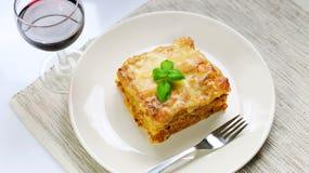 Lasagna με την από τη Μπολώνια σάλτσα στο άσπρο πιάτο με το κρασί Στοκ φωτογραφίες με δικαίωμα ελεύθερης χρήσης