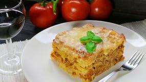 Lasagna με την από τη Μπολώνια σάλτσα στο άσπρο πιάτο με το κρασί Στοκ Εικόνες