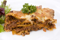 Lasagna. Piece of lasagna al forno with some salad Royalty Free Stock Images