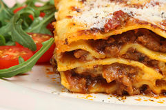 Lasagna al Forno. Beef lasagne topped with grated parmesan and served with rocket and tomato salad Stock Images