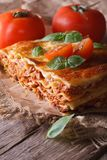 Lasagna with basil and tomatoes on an old table, vertical rustic. Italian lasagna with basil and tomatoes on an old table, vertical rustic style Royalty Free Stock Photos