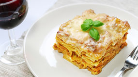 Lasagna with bolognese sauce on white plate with wine Stock Image