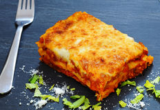 Lasagna. Bolognese served on slate plate garnished with parmesan and celery leaves royalty free stock photography