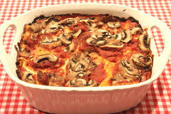 A lasagna casserole with mushrooms. An old fashioned lasagna Italian dinner with mushrooms on top and a red gingham tablecloth Stock Image